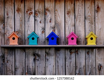 Colorful small multicolored birdhouses on a barn wall