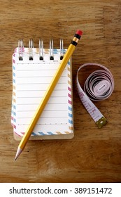 Colorful small spiral notebook, pencil and measuring tape on a wooden table