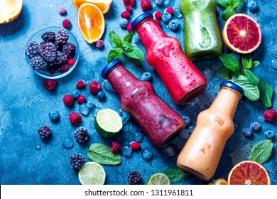 Colorful smoothie in bottles, with spinach, berries, lime. Detox diet fresh vegan drink for breakfast or snack.