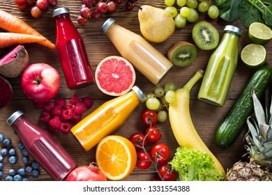 Colorful smoothies in bottles and fresh fruits and vegetables on woodentable, top view.