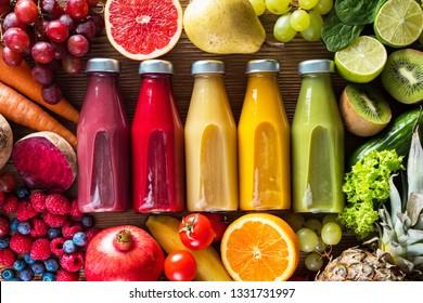 Fregaderos coloridos en botellas y frutas y verduras frescas sobre una mesa de madera, vista superior.