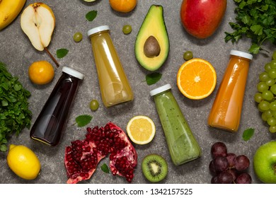 Colorful smoothies in bottles with fresh tropical fruit and vegetables on concrete background, top view. Flat lay.  Healthy, clean eating, vegan, vegetarian, detox, dieting food concept.