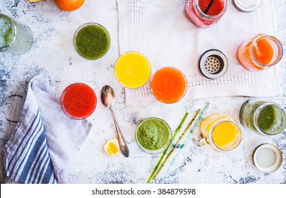 Colorful Smoothies in glass jar. Blended green,yellow and purple smoothie with chia and sesame seeds and stone white tabletop. Breakfast and detox concept. top view.