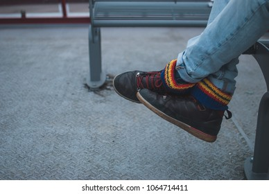 Colorful socks inside brown travel shoes of a man sitting on grey metal bench of public transport boat in Hamburg, Germany
