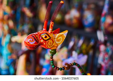 Colorful souvenir background. Souvenir shop selling souvenirs and handicrafts. Handmade wooden giraffe. Sale of souvenirs. Funny giraffes with bright colorful patterned. Selective focus.