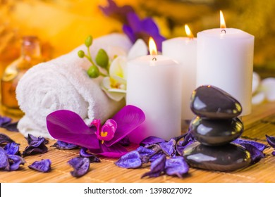 Colorful spa setting with beautiful flowers and burning candles place for relaxation
