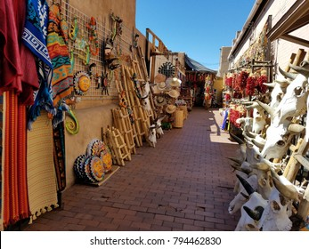 Colorful Spanish/Mexican, Southwestern Art and Textiles for Sale, Outdoors on a Side Alleyway, with Blue Skies and Bright Artwork on Both Sides of Alley; Travel, Tourism, Shopping
