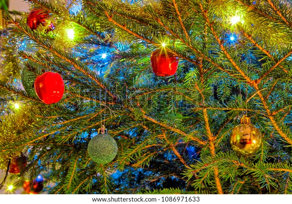 Colorful sparkling christmas tree. Red, green and golden decorations on green branches.