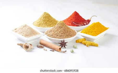 colorful spices in ceramic containers on a wooden background.