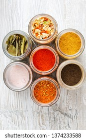 Colorful spices and dried vegetables in jars. Mixtures of spices standing on the kitchen counter.