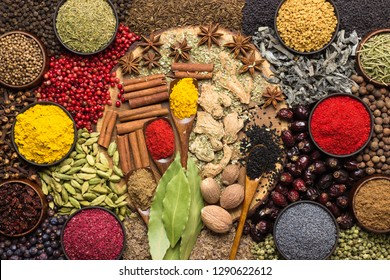 Colorful spices and herbs background. Large set seasonings scattered on table.