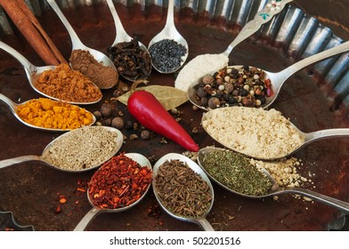 Colorful spices in metal spoons in old baking dish on wooden table.
