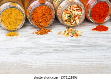Colorful spices pouring out of lying lying jars. Spices and free space on a wooden countertop. Lyophilized vegetables, ground paprika, curry and a mixture of spices.