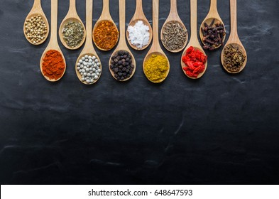 colorful spices in wooden spoon on black stone back ground with copy space for back ground.