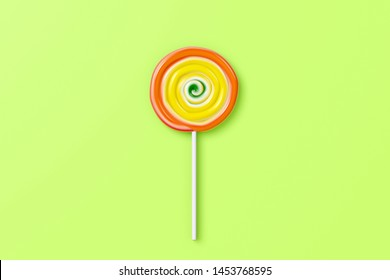 Colorful spiral lolipop on green pastel color background.sweet candy concept