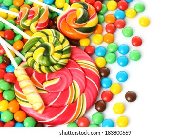 Colorful spiral lollipop with chocolate coated candy on white background
