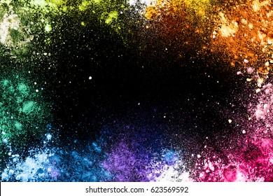 Colorful splashes of rainbow dust on a black background