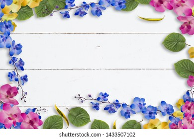 Colorful spring flower and leaf border or frame on white painted wood with central copy space with pink and blue artificial flowers
