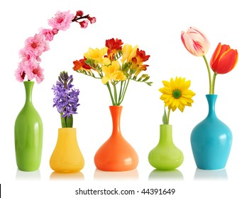 Colorful spring flowers in bright vases isolated on white