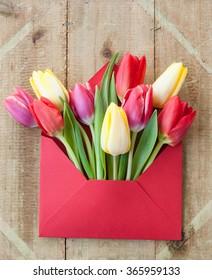 Fleurs printanières colorées dans une enveloppe, concept de distribution de fleurs