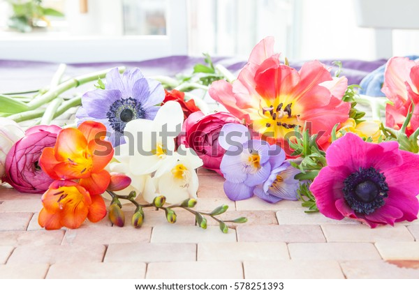 Colorful spring flowers on a rustic stone tile background