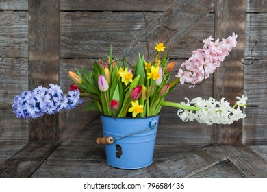Colorful spring flowers in vintage blue bucket