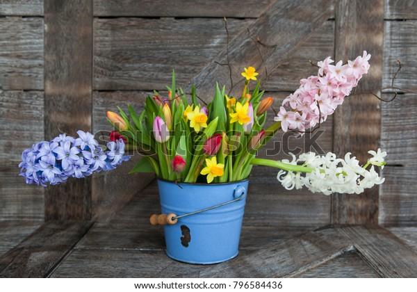 Colorful spring flowers in vintage blue bucket