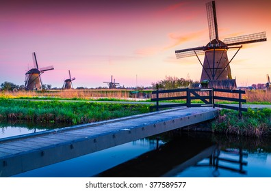Colorful spring scene in the famous Kinderdijk canals with windmills, UNESCO world heritage site. Sunset in Dutch village Kinderdijk, Netherlands, Europe.