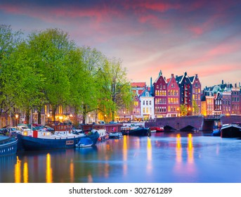 Colorful spring sunset on the canals of Amsterdam. Authentic Dutch architecture in the capital and most populous city of the Netherlands.