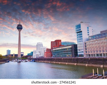 Colorful spring sunset of Rhein river at night in Dusseldorf. Rheinturm tower and a bridge in the soft evening light, Nordrhein-Westfalen, Germany, Europe.