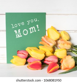 Colorful Spring Tulips in red and Yellow with a green card with love you, Mom wishes stamped on it. Square with white shiplap board background with room or space for your text, copy or design