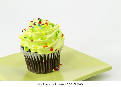 Colorful sprinkles on green frosting of chocolate cupcake on square plate with white background