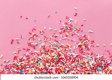 Colorful sprinkles on a pink background, top view with copy space