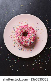 Colorful sprinkles poured over a pink frosted sugar bomb doughnut placed on a pink plate set on a shiny black paper background.