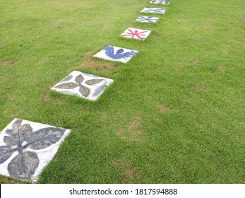 Colorful square concrete plates on the grass field as a walkway in a garden