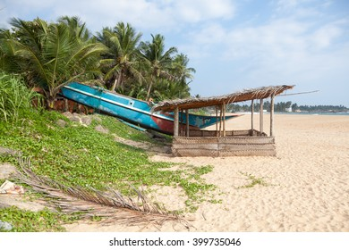 Colorful Sri Lankan fishing boat on sandy beach with palm trees in the background and a little hut in the foreground.