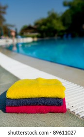 Colorful stacked towels near the swimming pool