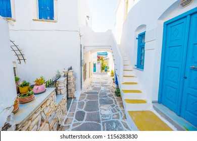 Colorful stairs in narrow street with white houses and blue colored windows. Old rustic Greek house exterior
