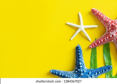 Colorful starfishes on yellow background with free space. Travel and summer concept.