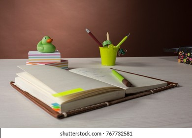 colorful stationery for business, creativity and study. on the table is an open notebook. Back is an ornamental bucket with handles and a rubber duckling