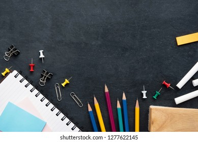 Colorful stationery and educational supplies on blackboard background top view border design with copy space
