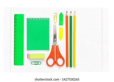 Colorful stationery set on white squared paper as background. Top view, flat lay.
