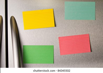 Colorful sticky notes on a stainless steel refrigerator.