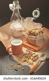Colorful still life of round cookie with peanuts and chocolate icing, orange cup of milk, glass jars and jam on crumpled paper and wooden plank