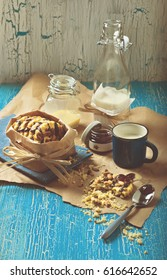 Colorful still life of round cookie with peanuts and chocolate icing, blue cup of milk, glass jars and jam on crumpled paper and wooden plank