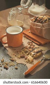 Colorful still life  side view of round cookie with peanuts and chocolate icing, orange cup of milk, glass jars and jam on crumpled paper and wooden plank