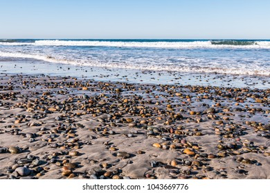 Colorful stones dot the beach at South Carlsbad State Beach in San Diego, California.