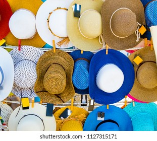 Colorful straw hats hanging on the market stall outdoor. Bright summer woman hats for sale