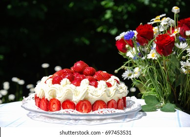 Colorful strawberry cake and a bouquet with summer flowers