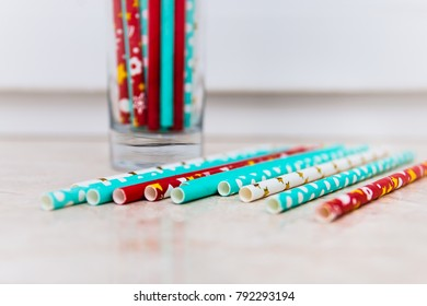 colorful straws in a glass and on a table
